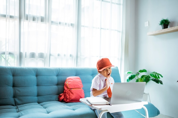 Aluna da escola primária uniformizada acenando para a professora e amiga durante a aula online