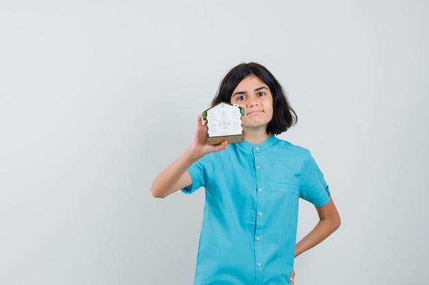 Aluna de camisa azul mostrando o modelo da casa e parecendo confiante
