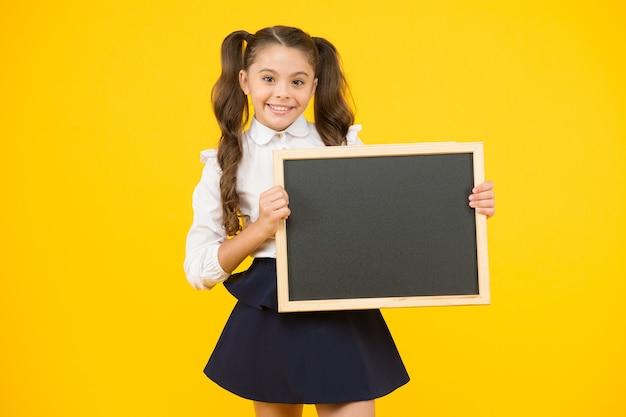 Aluna de colegial informando você. menina da escola segurar o espaço da cópia do quadro em branco. anúncio e promoção. veja isso. uniforme escolar de menina segura quadro-negro. de volta ao conceito de escola. não esqueça.