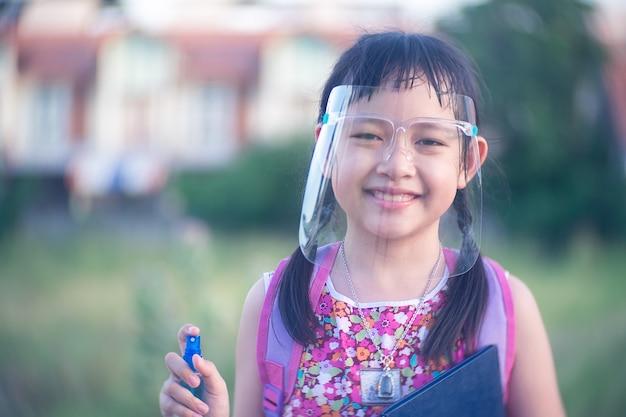 Aluna de criança pequena usando escudo facial durante ela voltar para a escola depois da quarentena de 19 de covid