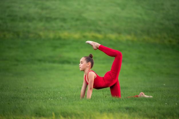 Aluna de macacão vermelho brilhante pratica ginástica na grama, fazendo exercícios de alongamento