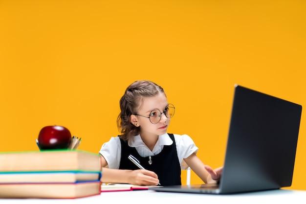 Aluna de óculos, escrevendo e sentada no laptop durante a aula on-line, aprendizagem em escolas distantes