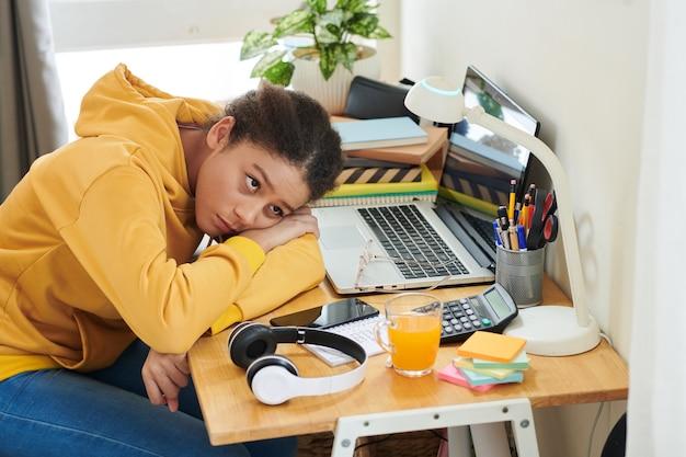 Aluna de raça mista chateada com cabelo afro inclinada a cabeça sobre os braços cruzados na mesa com laptop e fones de ouvido e olhando para a lâmpada