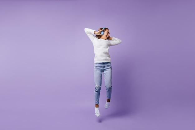Aluna de sorte alegre pulando. retrato de corpo inteiro de menina na camisola branca da moda e jeans azul claro.