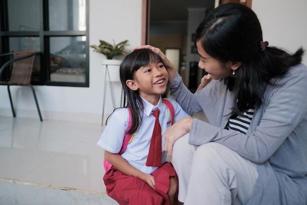 Aluna do primário feliz em casa depois da escola e conversar com sua mãe