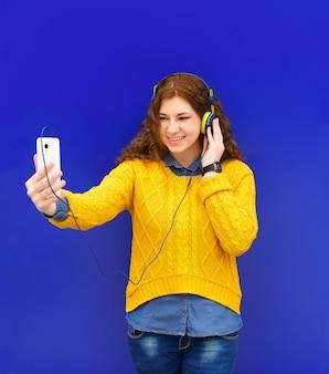 Aluna em fones de ouvido, ouvindo música, tirando foto