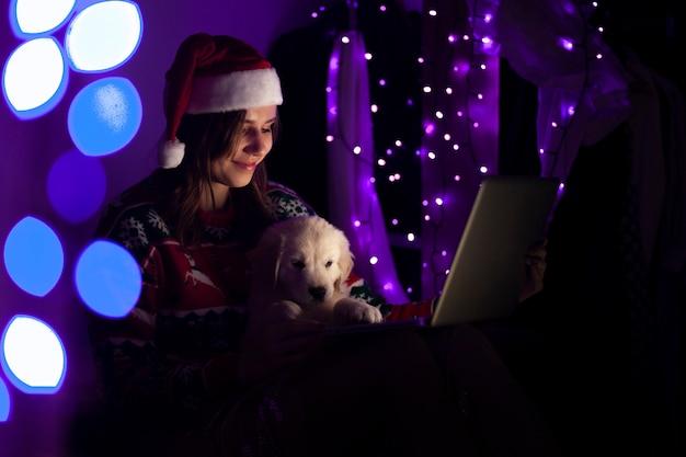Aluna em roupas de natal fica em casa à noite com um cachorrinho e um laptop