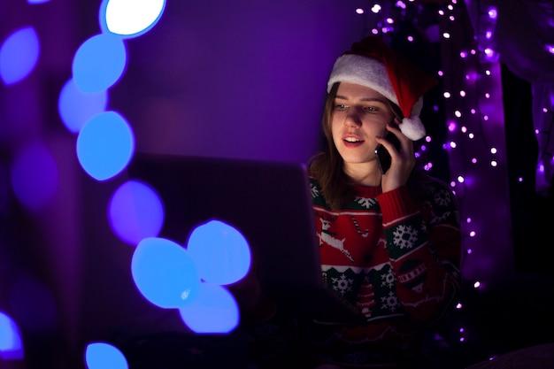 Aluna em roupas de natal, sentado à noite com um laptop e falando ao telefone