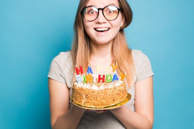 Aluna encantadora, alegre, louca, jovem, com chapéu de papel de felicitações, segurando um bolo de feliz aniversário em