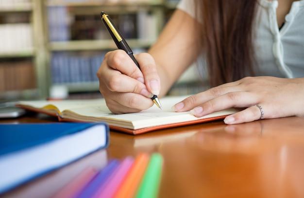 Aluna escrevendo livro dentro da biblioteca