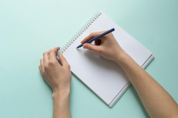 Aluna, escrevendo o plano de organização no livro didático para a educação, usando a caneta para fazer anotações.
