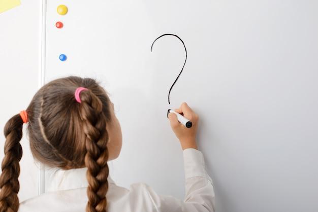 Aluna escrevendo um grande ponto de interrogação em um quadro branco