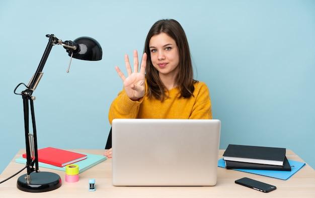 Aluna estudando em sua casa na parede azul feliz e contando quatro com os dedos
