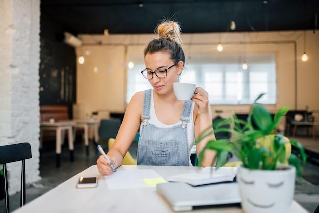 Aluna estudando no café. escrevendo com caneta e segurando uma xícara.