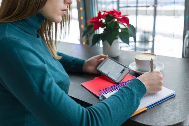 Aluna estudando no café usando smartphone e notebook