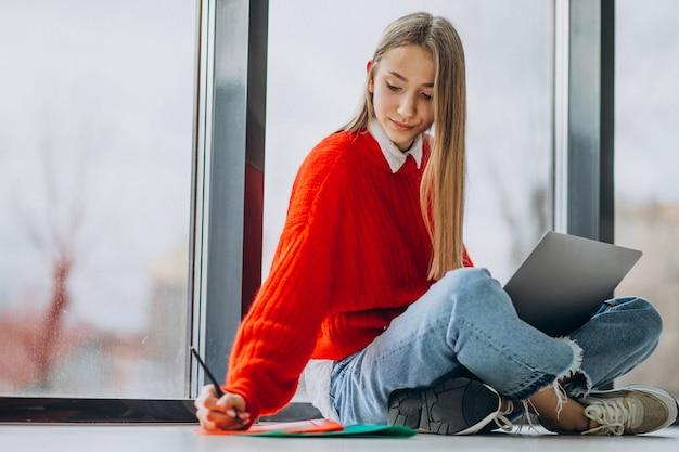 Aluna estudando no computador pela janela