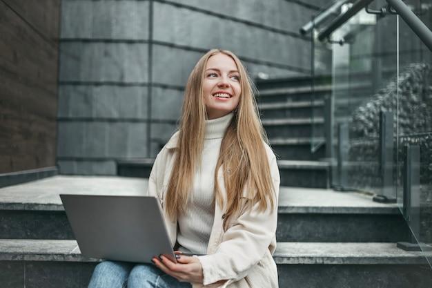 Aluna feliz caucasiana sentada na escada perto da universidade com um laptop, sorrindo e olhando para o lado. mulher jovem que trabalha online perto do escritório.