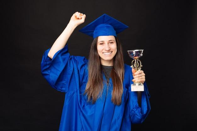 Aluna feliz celebrando a formatura e segurando a taça do campeão