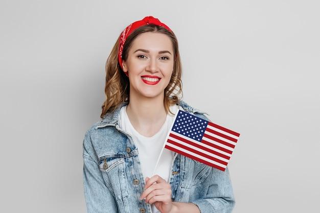Aluna feliz com batom vermelho segura uma pequena bandeira americana e sorrisos isolados sobre a parede cinza. garota segurando a bandeira dos eua, dia da independência de 4 de julho, copie o espaço