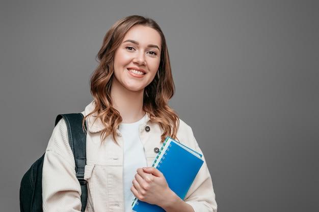Aluna feliz com mochila que um caderno sorri isolado sobre o banner da web de parede cinza escuro. o conceito de educação aprende inglês