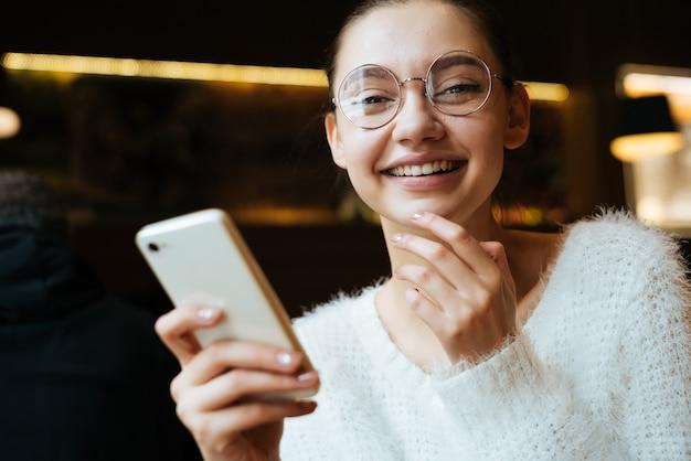 Aluna feliz de óculos e jaqueta branca segurando um smartphone, rindo, em um café