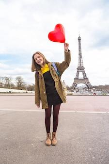 Aluna feliz e sorridente com um balão em forma de coração no plano de fundo da torre eiffel em paris. frança