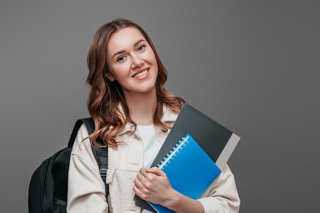 Aluna feliz em roupas brilhantes, segurando um bloco de notas do caderno uma pasta nas mãos dela sorrindo e olhando para a câmera em uma parede cinza escura para texto