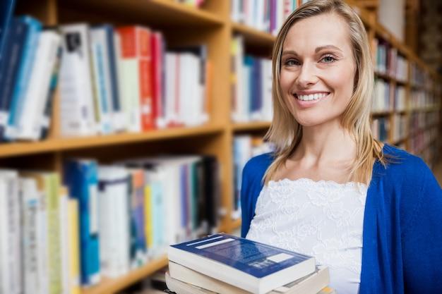 Aluna feliz levando livros na biblioteca da universidade