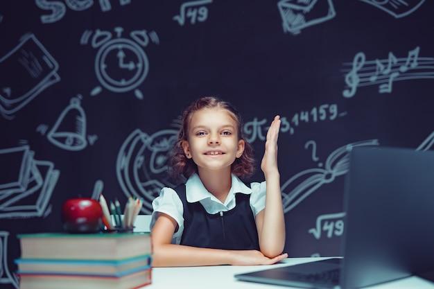 Aluna feliz levantando a mão sentada no laptop durante a aula online de aprendizagem em escolas distantes