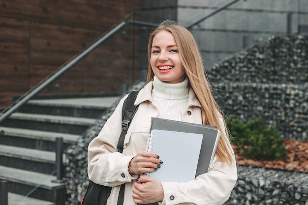 Aluna feliz segurando pastas de caderno nas mãos, sorrindo no prédio da faculdade