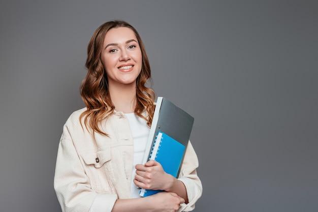 Aluna feliz, segurando um bloco de notas do caderno uma pasta nas mãos dela sorrindo e olhando para a câmera em uma parede cinza escura. jovem trabalhador trabalhador empresa freelancer