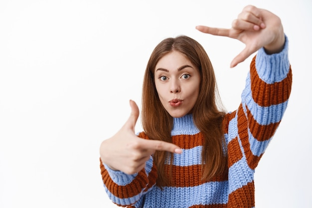 Aluna fofa fazendo gestos de molduras com as mãos como se estivesse fotografando para a câmera, em pé contra uma parede branca