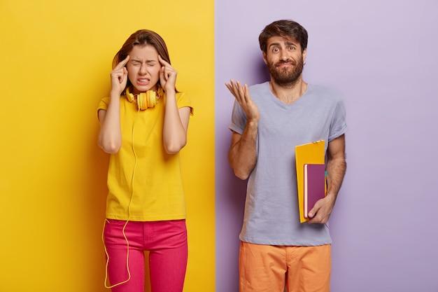 Aluna frustrada mantém o dedo indicador nas têmporas, sofre de dor de cabeça, colega de grupo masculino em dúvida segura cadernos