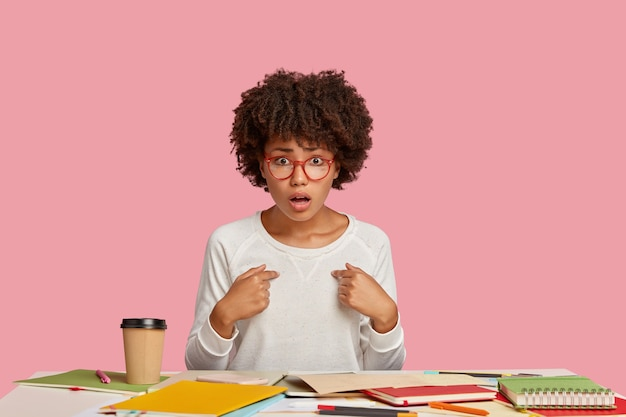 Aluna indignada posando na mesa contra a parede rosa
