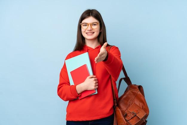 Aluna jovem adolescente segurando livros sobre parede azul aperto de mão depois de bom negócio