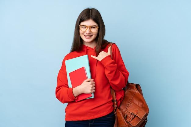 Aluna jovem adolescente segurando uma salada sobre parede azul, fazendo gesto de telefone