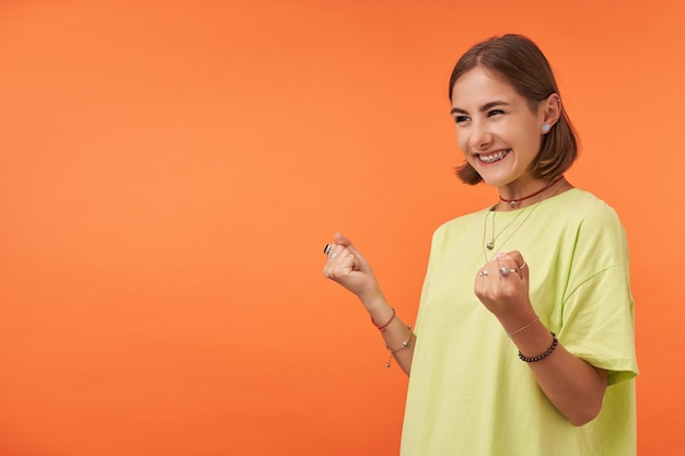 Aluna, jovem animada com o que ela sabe. observando à esquerda no espaço da cópia sobre a parede laranja. vestindo camiseta verde, colar, pulseiras e anéis