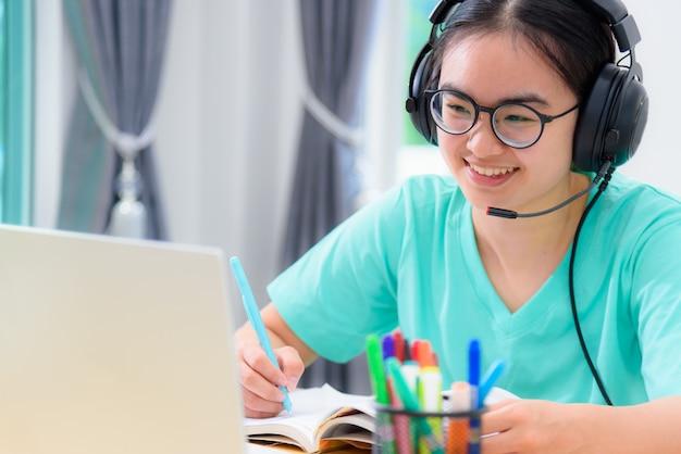 Aluna jovem asiática com fones de ouvido e óculos, escrevendo sobre o livro, olhando para a videoconferência em computadores laptop, uma garota fica feliz em fazer o curso on-line de ensino à distância da universidade na internet