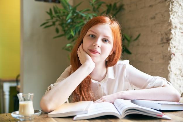 Aluna jovem atraente com pele branca e longos cabelos ruivos está lendo livros, estudando, rodeado por livros em uma mesa em um café, posando para um retrato em luz natural