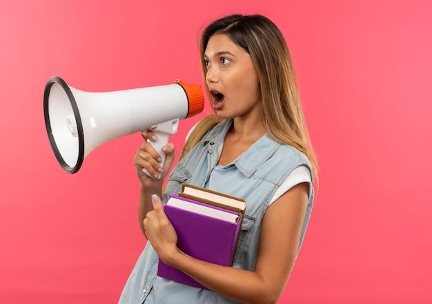 Aluna jovem bonita vestindo uma bolsa de costas segurando livros, olhando para o lado e falando por alto-falante, isolada em um fundo rosa com espaço de cópia