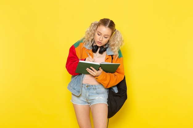 Aluna jovem com roupas modernas escrevendo notas em amarelo