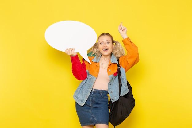 Aluna jovem com roupas modernas segurando uma enorme placa branca com um sorriso amarelo
