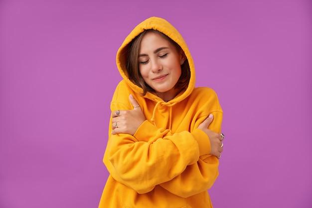Aluna, jovem de cabelos castanhos curtos, se abraça, sentindo-se aconchegante e confortável, olhos fechados em pé sobre a parede roxa. vestindo moletom laranja e anéis