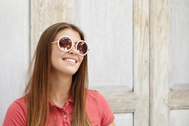 Aluna jovem e atraente caucasiana sorrindo alegremente com seus dentes brancos