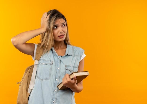 Aluna jovem e bonita confusa usando uma bolsa de costas, segurando um livro, colocando a mão na cabeça, olhando para o lado isolado em laranja com espaço de cópia