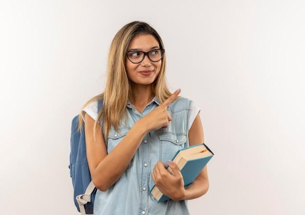 Aluna jovem e bonita satisfeita usando óculos e bolsa com as costas segurando o livro e apontando para o lado isolado na parede branca