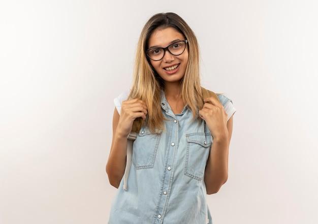 Aluna jovem e bonita sorridente usando óculos e uma mochila segurando as alças da mochila, isoladas na parede branca