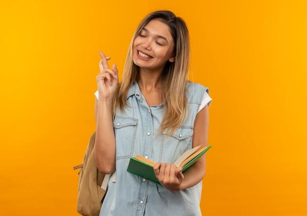 Aluna jovem e bonita sorridente usando uma bolsa de costas, segurando um livro aberto, cruzando os dedos com os olhos fechados, isolada na parede laranja