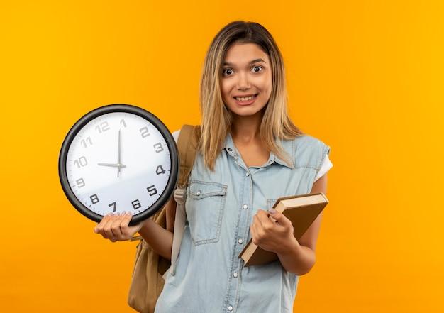 Aluna jovem e bonita sorridente usando uma bolsa de costas segurando um livro e um relógio isolado na parede laranja