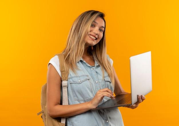 Aluna jovem e bonita sorridente vestindo uma bolsa de costas segurando e usando um laptop isolado na parede laranja